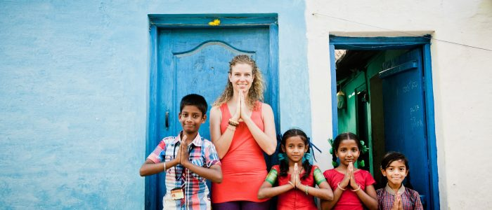 Josien in prayer pose with 4 other people to start the yoga class